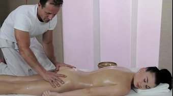 Oiled sexy brunette fucks muscled masseur on a table